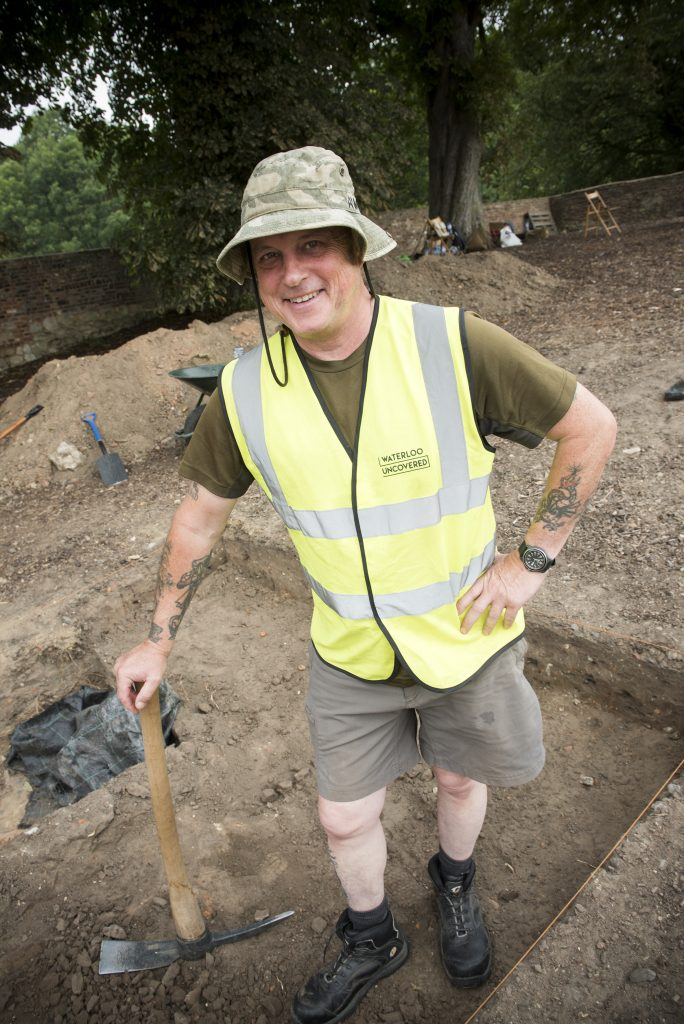 Jim Howdle on site in 2019, holding a mattock and standing in a trench