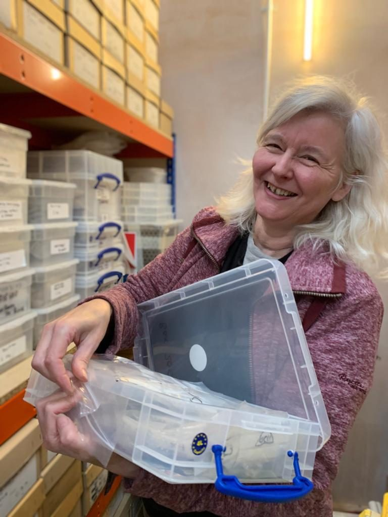 Finds Officer Hillery Harrison stands in front of a shelf of boxed finds in our finds lab