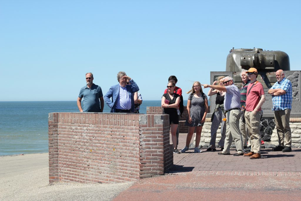 A group of summer school participants on a field trip, standing in front of a war memorial on the coast