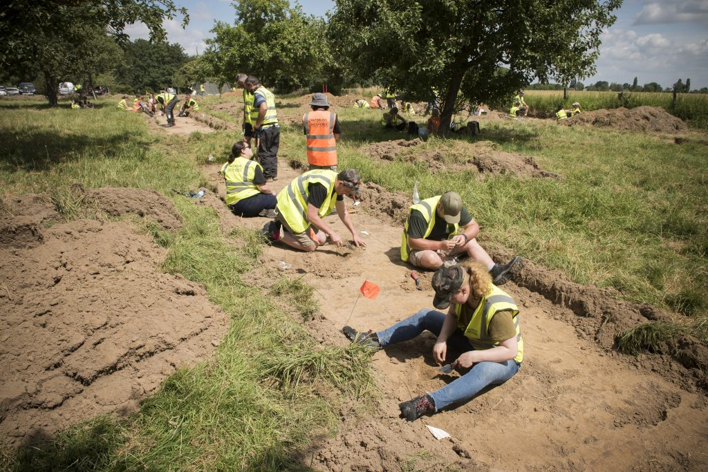 Team members digging up a trench in the orchard of Mont Saint Jean farm