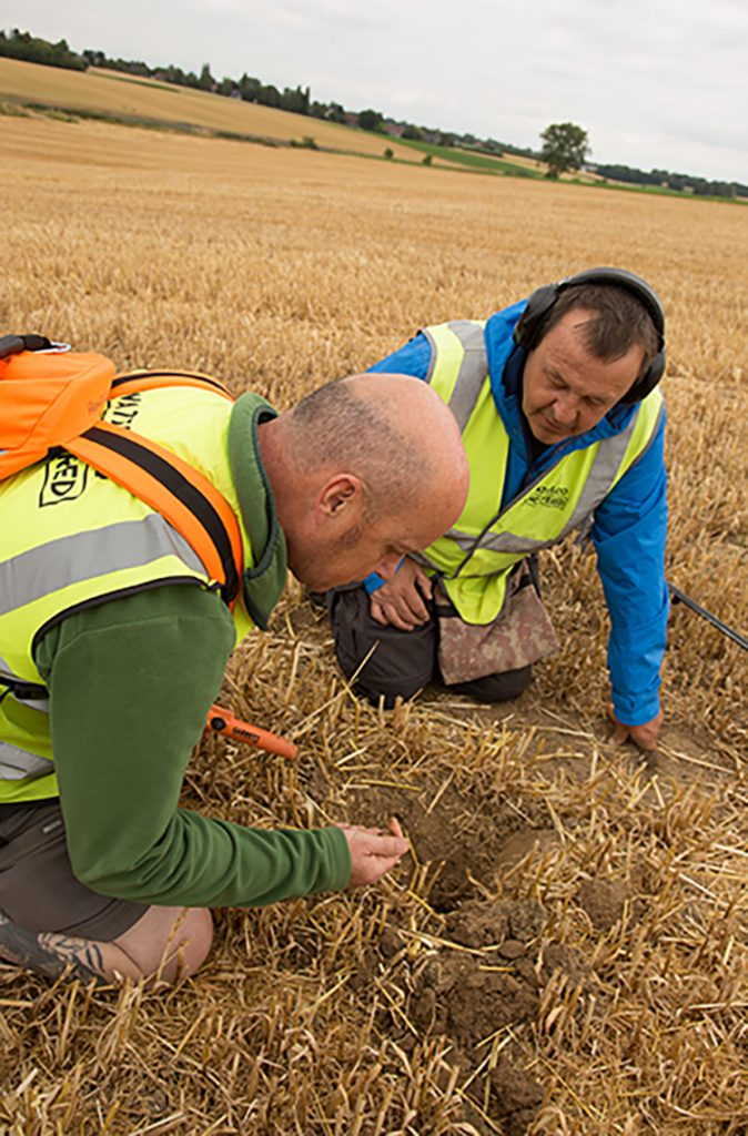 Veteran Jim Howdle and metal detector specialist Gary Craig dig up a find on site in 2019