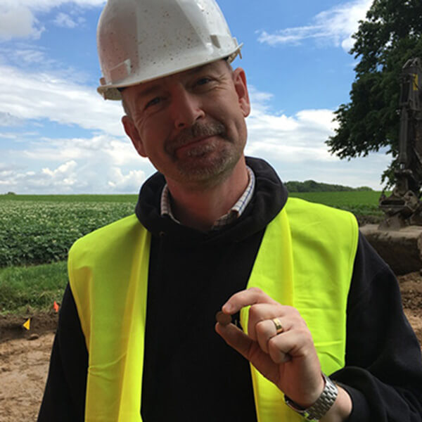 Welfare Officer and veteran David Ulke, wearing a hardhat and high vis jacket, holding a button he discovered at Hougoumont