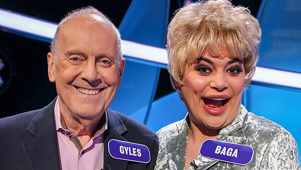 Gyles Brandreth and drag queen Baga Chipz on Pointless Celebrities, smiling and wearing large name tags