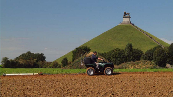 A geophysicist conducts a survey using Electromagnetic Induction, which is attached to the back of a quad bike. He drives the quad bike in front of the Lion Mound near Waterloo.